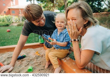 Portrait Of Happy Family Having Fun In Sandbox. Mid Adult Parents And Their Toddler Daughter Sitting