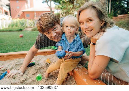 Portrait Of Joyful Family Sitting In Sandbox. Mid Adult Man And Woman Playing With Toddler Daughter