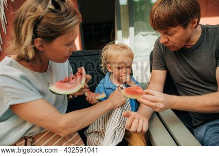 Family With Little Girl Eating Watermelon Together. Mid Adult Parents Sitting In Chairs And Feeding