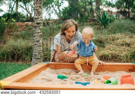 Happy Mother Playing With Her Little Daughter In Sandpit. Girl Sitting In Sandbox And Putting Sand I