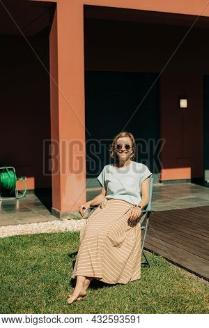 Portrait Of Happy Woman Sitting On Chair At House. Mid Adult Lady Wearing Sunglasses Resting On Back