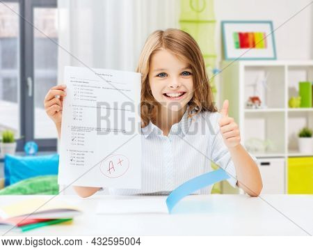 education and school concept - happy smiling student girl with school test and A grade showing thumbs up over home room background