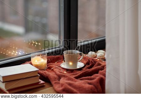 season, leisure and objects concept - cup with mesh tea infuser ball, books, garland lights and candle burning on window sill at home