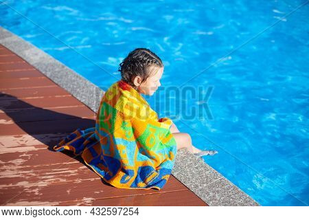 Child Is Sitting By Pool. Little Girl With Braided Pigtails Is Sitting On Side Of Pool And Wrapped I