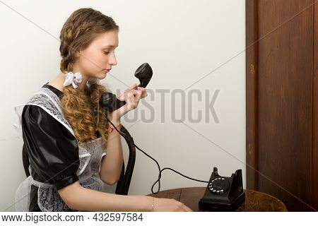 Pretty School Girl Using A Vintage Old Phone. Portrait Of Girl Graduate With Braids Wearing Retro Us