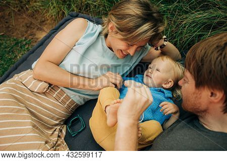 Cheerful Parents Tickling Child Lying Outdoors. Happy Couple Lying On Mattress Together With Little