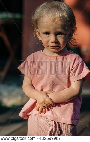 Portrait Of Sad Baby Girl Standing Outdoors. Cute Toddler Wearing Pink Tshirt. Childhood Concept