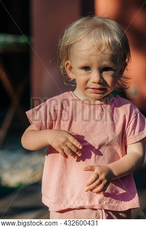 Portrait Of Crying Toddler Girl Standing Outdoors. Cute Little Child Wearing Pink Tshirt. Childhood