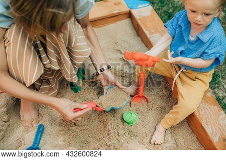 Mother And Child Playing Together In Sandpit. Woman Playing With Little Daughter On Playground Outdo