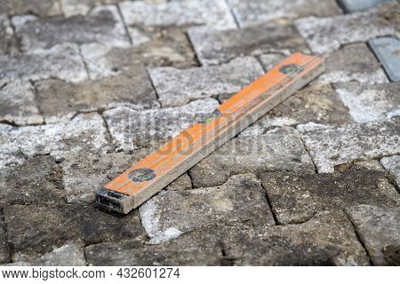 Orange Spirit Level On Newly Constructed Street Work Consisting Of Concrete H Vowels