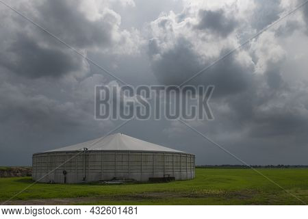 Round Concrete Manure Silo On A Meadow In The Summer With Threatening Cloudy Skies In The Netherland