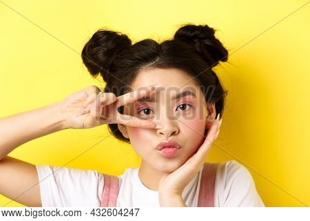 Close-up Of Cute Asian Woman With Bright Glamour Makeup, Long Fingernails, Showing V-sign And Poutin