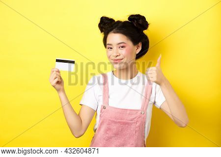 Shopping. Stylish Asian Glam Girl Showing Thumb Up And Plastic Credit Card, Standing On Yellow Backg