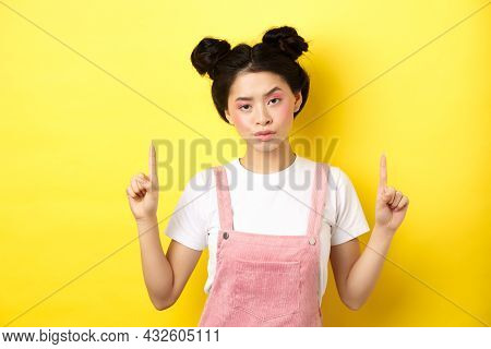 Annoyed And Tired Asian Girl With Pink Glamour Makeup, Pointing Fingers Up And Look Bothered, Standi