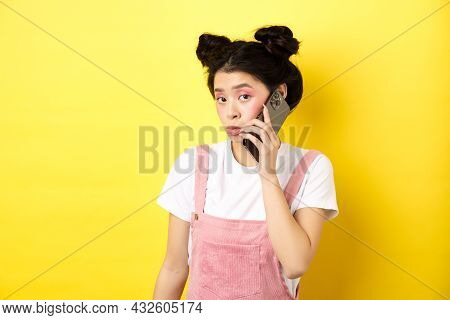 Cute Teen Girl Talking On Smartphone, Making Silly Pouting Face And Look Timid At Camera, Standing W