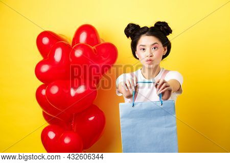 Happy Valentines Day. Cute Asian Girlfriend Giving Lover A Gift, Stretch Out Hands With Shopping Bag
