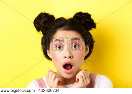 Head Shot Of Shocked Asian Girl With Hairbuns And Glamour Makeup, Open Mouth And Looking Startled At