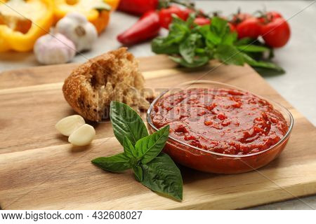 Delicious Adjika Sauce In Glass Bowl With Bread And Ingredients On Wooden Board, Closeup