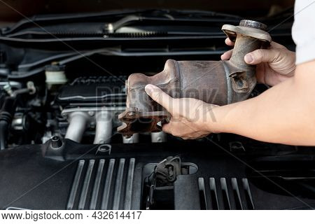 Close Up Old Catalytic Converter In Hand Technician Remove From Engine Gasoline Car Dust Clogged Con