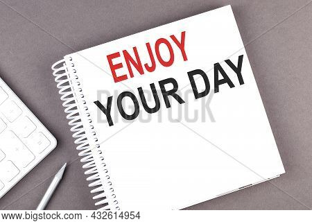 Enjoy Your Day Text On Notebook With Calculator And Pen