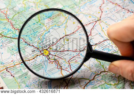 Map Of Sevilla (seville) In Spain Through Magnifying Glass, Concept Of Planning The Travel Itinerary