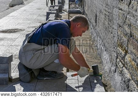 Saint Petersburg, Russia-september 2021. A Male Bricklayer In Construction Gloves Holds A Hammer To