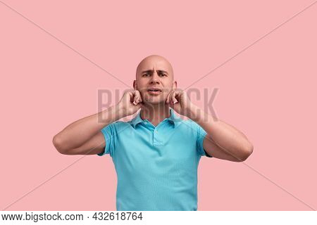 Displeased Bald Homosexual Man With Bristle Plugs Ears With Fingers, Does Not Want To Hear Loud Musi