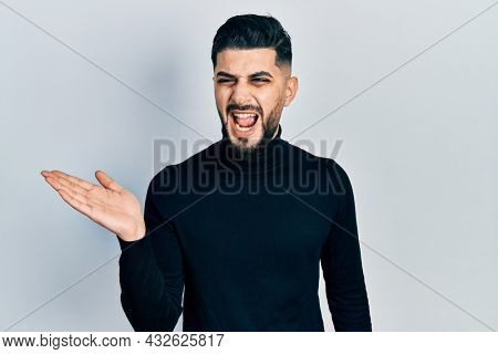 Handsome man with beard presenting with open palm angry and mad screaming frustrated and furious, shouting with anger. rage and aggressive concept.