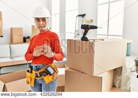 Middle age grey-haired woman wearing hardhat standing at new home disgusted expression, displeased and fearful doing disgust face because aversion reaction. with hands raised