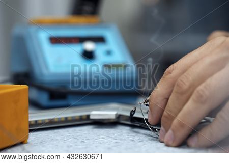 Wires Being Soldered Together With A Soldering Iron. Melting Solder Wire On Soldering Iron Tip