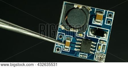 silicon electronic chip Tweezers and electronics chip Electronic chip isolated on dark blue
