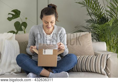 Young Woman In Her Living Room Looks Happy As She Unpacks A Small Cardboard Box Containing Something