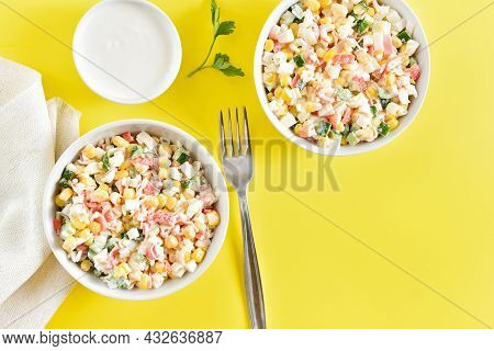 Imitation Crab Salad With Crab Sticks, Corn, Eggs, Cucumber And Rice In Bowls Over Yellow Background