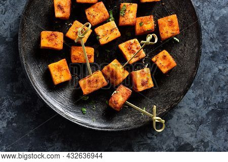 Close Up View Of Pan Fried Paneer. Indian Roasted Cottage Cheese Bites On Plate Over Blue Stone Back