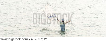 Panoramic Rear View Asian Fisher Man With Waterproof Wader And Hat Throwing A Cast Net In Freshwater