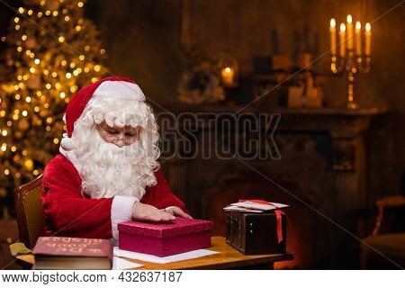 Workplace of Santa Claus. Cheerful Santa is conjuring over the gift box while sitting at the table. Fireplace and Christmas Tree in the background. Christmas concept.