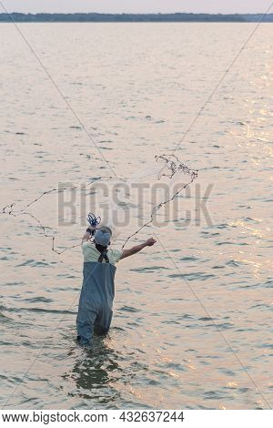 Unidentified Asian Fisher Man With Waterproof Wader And Hat Throwing A Cast Net At Sunrise