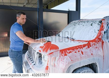 A Man Washes His Car With A Sponge At A Car Wash. Car In Foam