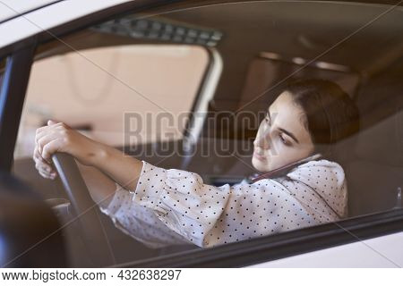 Unsafe Driving. Young Multiracial Woman Talking On The Phone While Driving. Distracted Driving. Fema