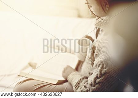 Reading In Bed. Young Woman Drinking Coffee And Reading A Book In The Bed. Multi-racial Female Reads
