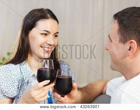 Happy Couple Enjoying A Glasses Of Red Wine