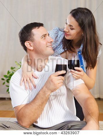 Couple Enjoying A Glasses Of Red Wine On Terrace