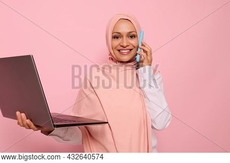 Portrait Of A Beautiful Arab Muslim Woman In Pink Hijab Talks On Mobile Phone, Looks At Camera, Smil
