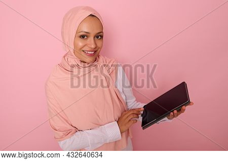 Arab Muslim Woman In Pink Hijab Smiles With Toothy Smile Looking At Camera, Posing On Pastel Colored