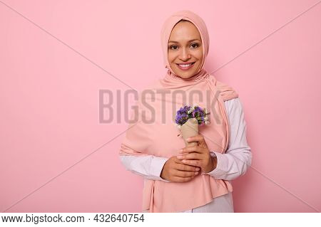 Isolated Portrait On Colored Background Of A Beautiful Muslim Arab Woman In Pink Hijab, Holding A Bo
