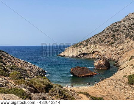 People on the beach visiting Shipwreck Olympia boat in Amorgos island during summer holidays, at the coastal rocky area, , Cyclades, Greece. Travel background