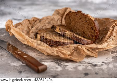 Three Slices Of Bread On Parchment Paper. Sliced Bread, An Iron Knife With A Wooden Handle, Lies Clo
