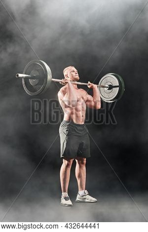 Weightlifting. A male weightlifter lifts the barbell with effort. Professional sports. Full length portrait on a black background.