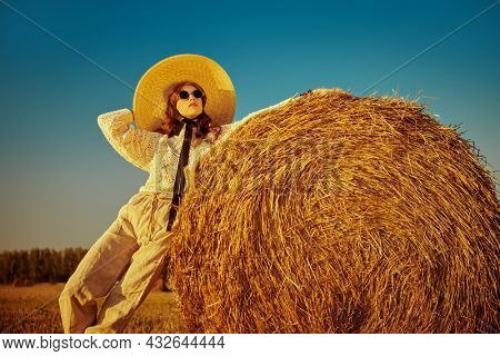 Summer and autumn fashion. Elegant fashion model in knitted sweater, wide-brimmed straw hat and round glasses poses by a haystack in the setting sun. Modern boho style.