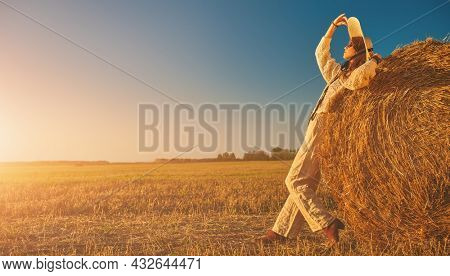 Full length portrait of a beautiful fashion model girl posing in boho style clothes in a field next to a haystack. Autumn and summer fashion, clothing and accessories.